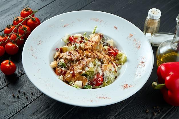 Salade césar avec croûtons, parmesan, poulet, oeuf dans un bol élégant blanc en composition avec des ingrédients