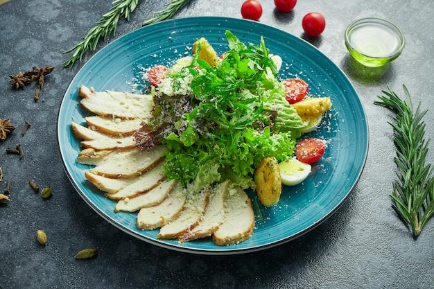 Salade césar avec croûtons, parmesan, poulet, œuf dans un bol élégant bleu en composition avec des ingrédients