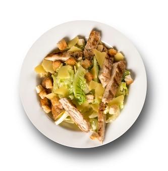 Salade césar avec croûtons et poulet grillé sur surface blanche.