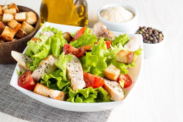 Salade césar dans un bol blanc sur une table en bois