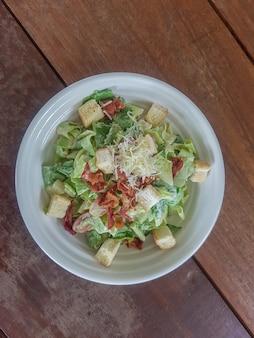 La salade césar dans un plat avec espace copie est un menu dans le restaurant.