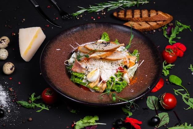 Salade césar avec filet de poulet grillé et tranches de bacon, avec tomates et sauce césar.