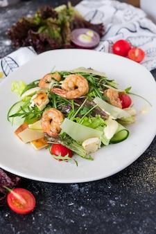 Salade césar fraîche aux crevettes sur une assiette blanche sur fond de pierre sombre