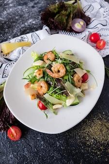 Salade césar fraîche aux crevettes sur une plaque blanche sur une pierre sombre.