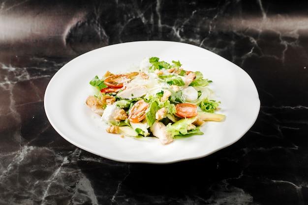 Salade césar avec des ingrédients mélangés à l'intérieur d'une assiette blanche sur un marbre noir.