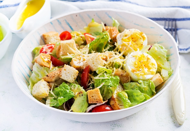 Salade césar avec laitue, poulet, avocat, tomates cerises et croûtons sur table lumineuse