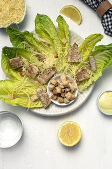 Salade césar maison avec romanine, fromage, croûtons, poulet, citron et sauce.