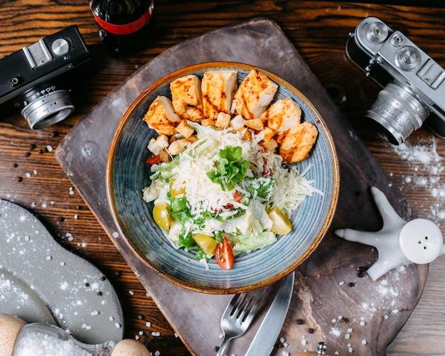 Salade césar avec poulet et parmesan dans un bol sur une table en bois