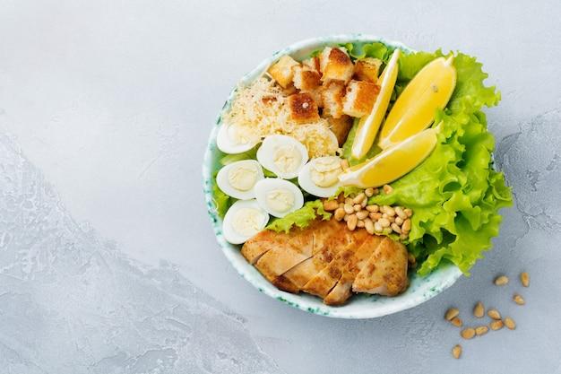 Salade césar traditionnelle avec des œufs de caille et des pignons de pin dans un bol en céramique léger sur une surface de béton gris
