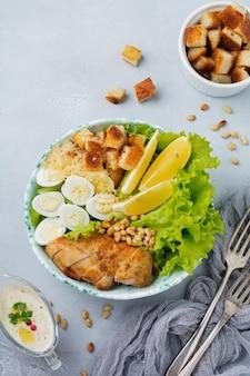 Salade césar traditionnelle avec des œufs de caille et des pignons de pin dans un bol en céramique légère sur une pierre grise ou une surface en béton
