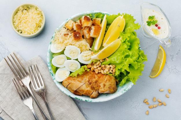 Salade césar traditionnelle avec œufs de caille et pignons de pin dans un bol en céramique légère sur une surface en pierre grise ou en béton. bol à lunch. mise au point sélective.