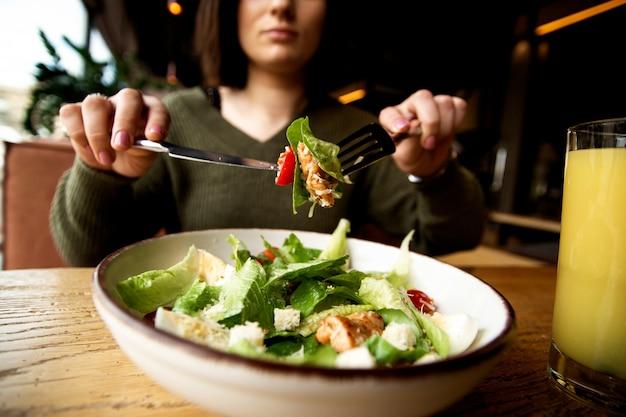 Salade césar et verre de joice orange. concept de nourriture saine. femme sérieuse en train de manger son repas.