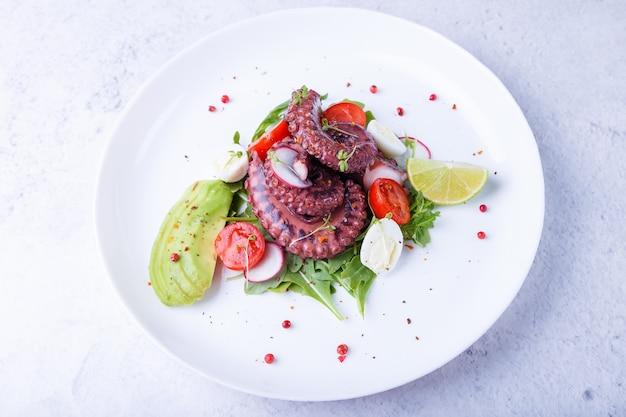 Salade chaude avec des tomates cerises de poulpe avocat roquette oeufs de caille radis et citron vert sur une plaque blanche
