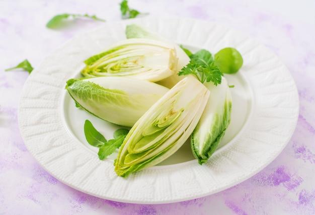 Salade de chicorée fraîche et saine (witloof) sur une assiette. menu diététique. nourriture saine.