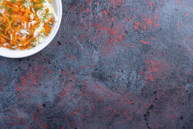 Salade de chou blanc et carottes sur un plateau sur fond de couleur sombre. photo de haute qualité