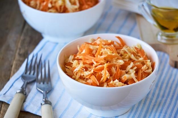 Salade de chou frais, carottes et huile d'olive dans un bol blanc sur une table en bois