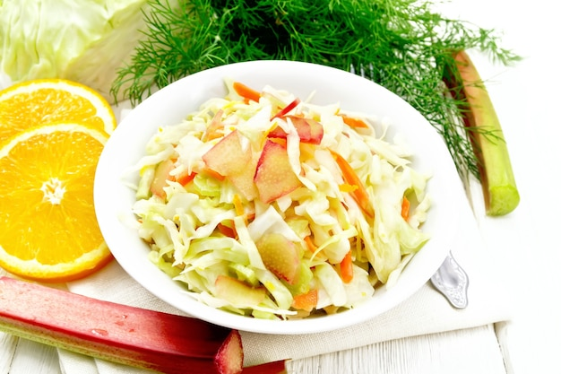 Salade de chou frais, carottes et rhubarbe avec jus d'orange, vinaigrette au miel et à la mayonnaise dans une assiette sur serviette, aneth et fourchette sur fond de planche de bois