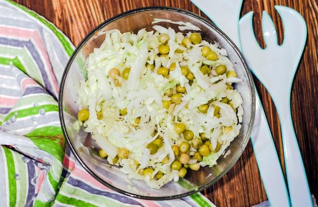 Salade de chou frais et petits pois en conserve dans un saladier