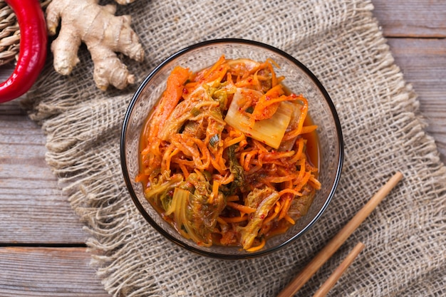 Salade de chou kimchi traditionnel bio fait maison avec des baguettes sur une table en bois. végétarien fermenté, concept d'aliments santé intestinaux préservés végétaliens