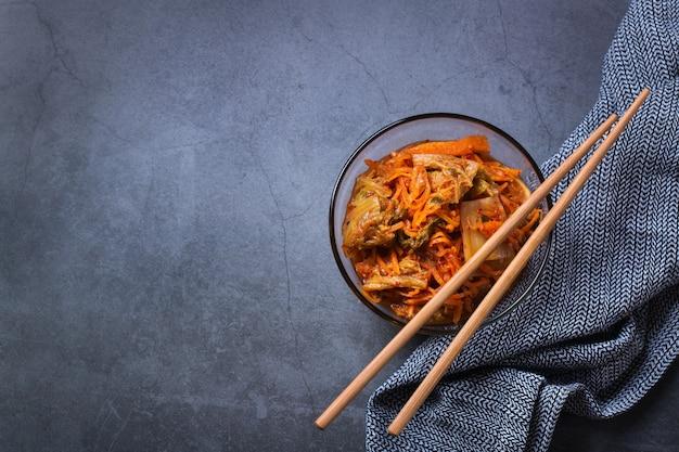Salade de chou kimchi traditionnel bio fait maison avec des baguettes sur une table sombre. végétarien fermenté, concept d'aliments santé intestinaux préservés végétaliens