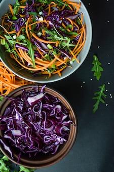 Salade de chou rouge, carottes et verts. décoré avec des légumes en tranches et des herbes. bandes de coupe.
