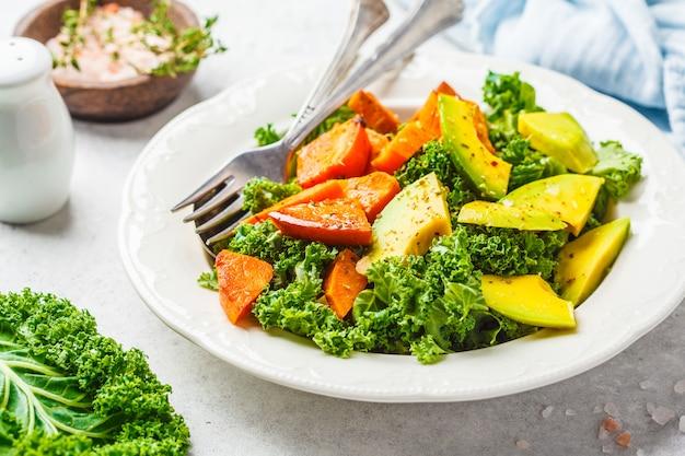 Salade de chou vert saine avec avocat et patates douces cuites au four.