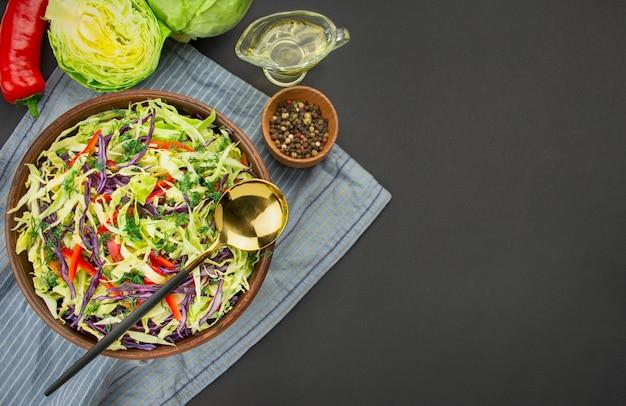 Salade de chou violet, chou blanc et poivrons dans un bol en argile foncé sur fond sombre