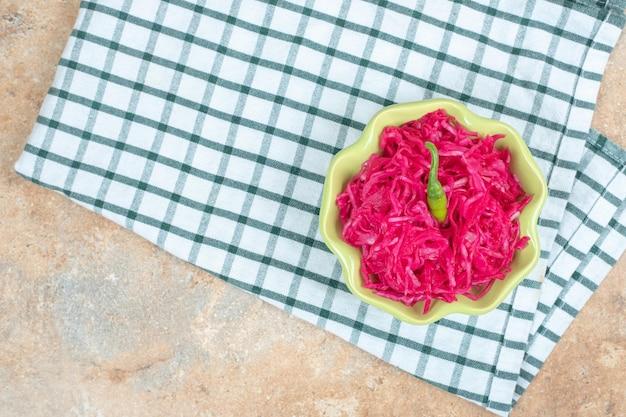 Salade de choucroute rouge dans un bol vert avec nappe.