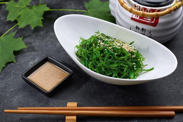 Salade de chuka aux concombres, graines de sésame et sauce, dans une assiette blanche, avec une théière japonaise, des baguettes et des feuilles d'érable, sur du béton noir
