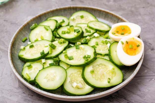 Salade de concombre frais, œufs à la coque et oignons verts sur une assiette sur la table