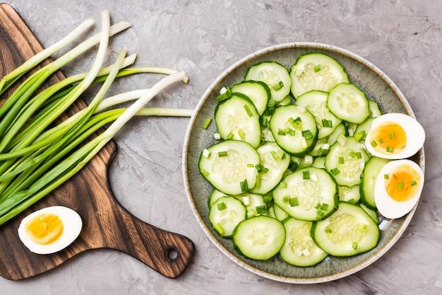 Salade de concombre frais avec des œufs à la coque et des oignons verts sur une assiette