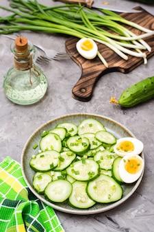 Salade de concombre frais, œufs à la coque et oignons verts dans une assiette et ingrédients pour la cuisson sur la table