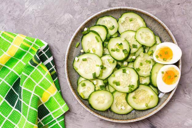 Salade de concombre frais prête à manger, œuf à la coque bouilli et oignons verts sur une assiette posée sur la table. vue de dessus