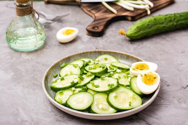 Salade de concombre frais prête à manger, œuf à la coque bouilli et oignons verts sur une assiette sur la table
