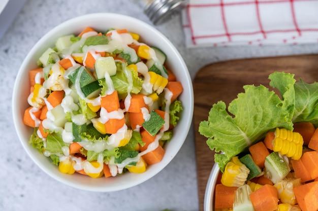 Salade de concombre, maïs, carotte et laitue dans une tasse blanche.