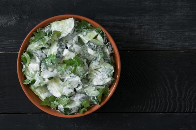 Salade de concombre avec vinaigrette au yaourt sur le bois noir avec fond