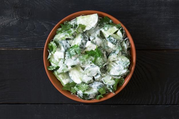 Salade de concombre avec vinaigrette au yaourt sur le bois noir