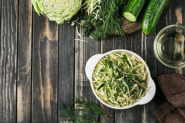 Salade de concombres fermentés frais et de chou sur un bois sombre.