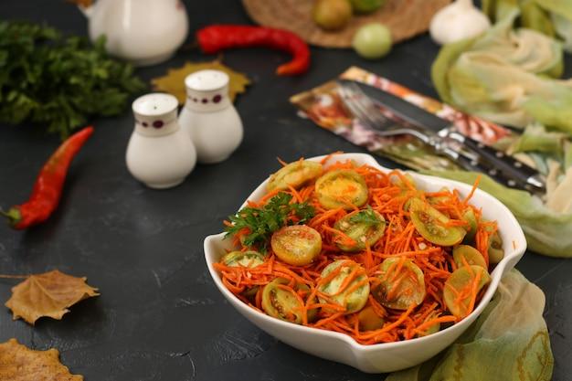 Salade coréenne avec des tomates vertes et des carottes dans un bol à salade blanc