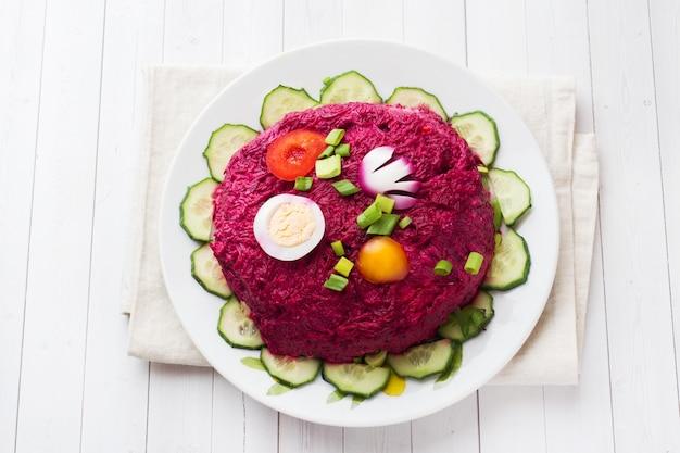 Salade en couches avec hareng et betteraves, carottes et pommes de terre et oeufs gros plan sur une assiette.