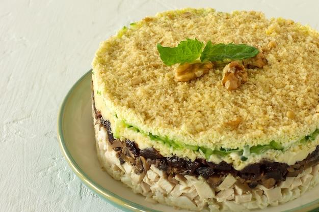 Salade en couches avec poulet, champignons, pruneaux, œufs, concombres et fromage servis sur une assiette sur fond blanc,