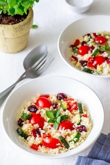 Salade de couscous aux tomates, poivrons, courgettes et canneberges. la nourriture végétarienne. régime. alimentation équilibrée.