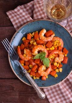 Salade de crevettes à la citrouille et au maïs sur l'assiette vintage bleue