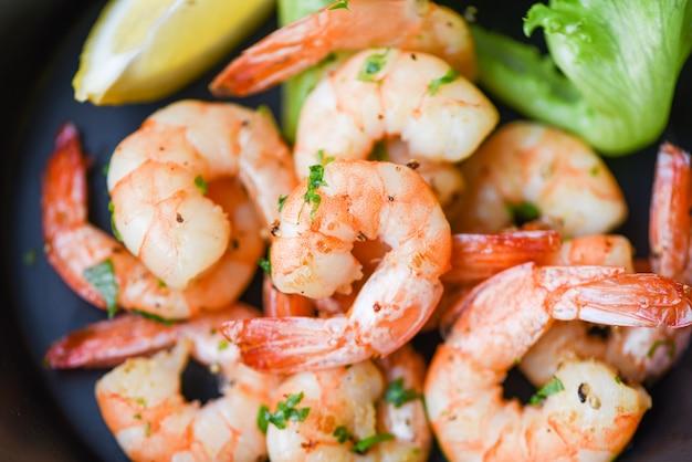 Salade de crevettes grillées délicieuses épices d'assaisonnement sur un bol de crevettes cuites appétissantes crevettes cuites au four, étagère de fruits de mer avec du citron et de la laitue