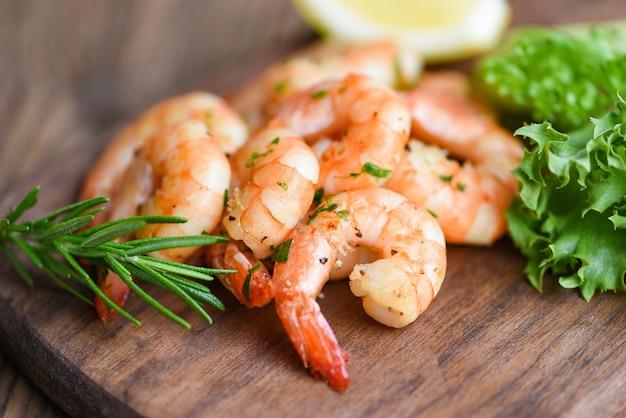Salade de crevettes grillées délicieuses épices d'assaisonnement sur fond de planche à découper en bois appétissants crevettes cuites crevettes cuites au four, étagère de fruits de mer avec romarin, citron et laitue