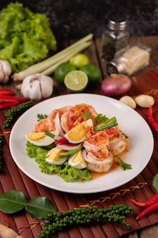 Salade de crevettes avec laitue aux œufs durs et oignons verts hachés dans une assiette blanche