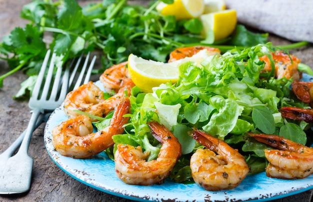 Salade de crevettes et laitue sur une plaque bleue
