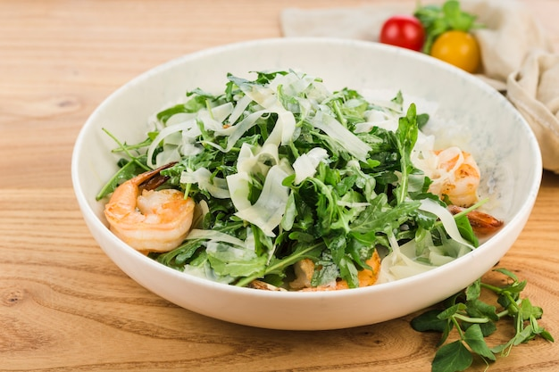Salade de crevettes, roquette et parmesan dans une assiette sur une surface en bois clair.