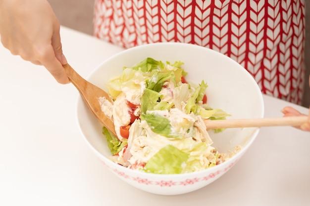 Salade de cuisine. des mains féminines mélangent les ingrédients.
