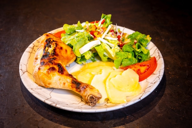 Salade avec cuisse de poulet et salade sur fond noir, sur une assiette blanche